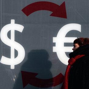 Знаки доллара и евро на стене пункта обмена валюты в Москве