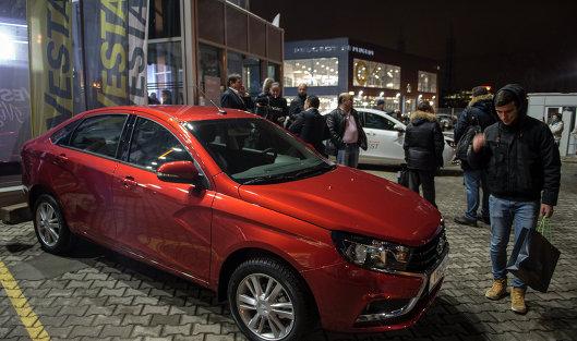 *Молодые люди осматривают автомобиль Lada Vesta после начала продаж в Москве