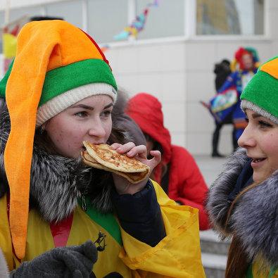 """Участники кушают блины во время массового масленичного гуляния """"Блинно-сырное веселье"""" в Белгороде"""