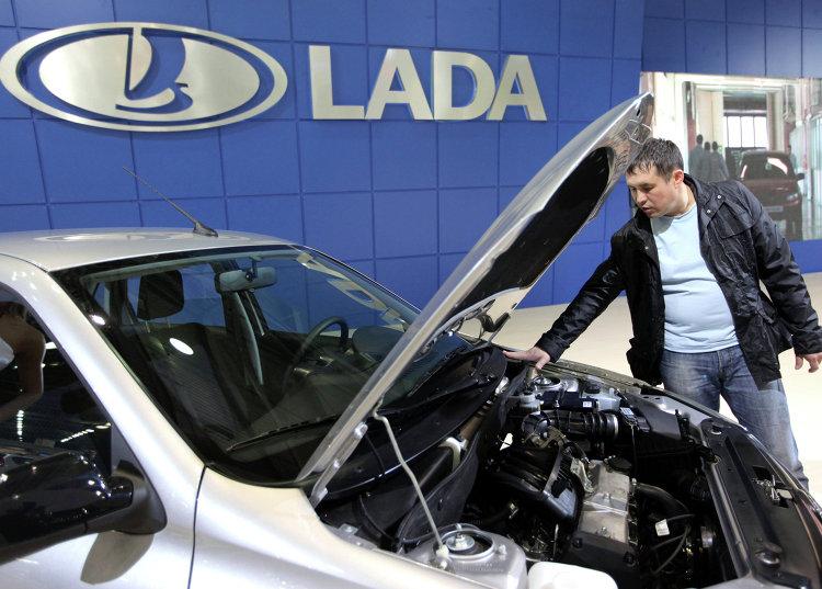 Посетитель осматривает автомобиль Lada Granta