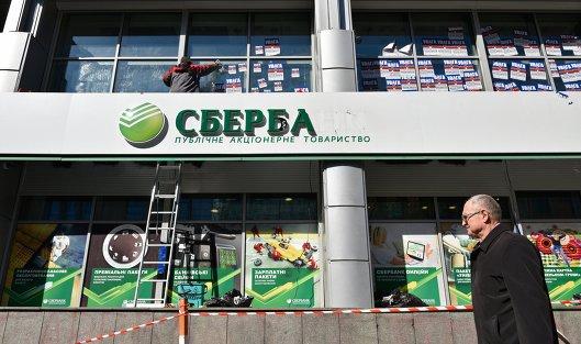 Рабочий очищает фасад центрального отделения дочернего предприятия Сбербанка России в Киеве от листовок. 28 марта 2017