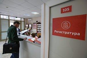 Посетитель у регистрационного стола в поликлинике №180 в Москве