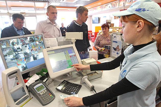 Продавец принимает оплату за топливо в магазине на автозаправочной станции
