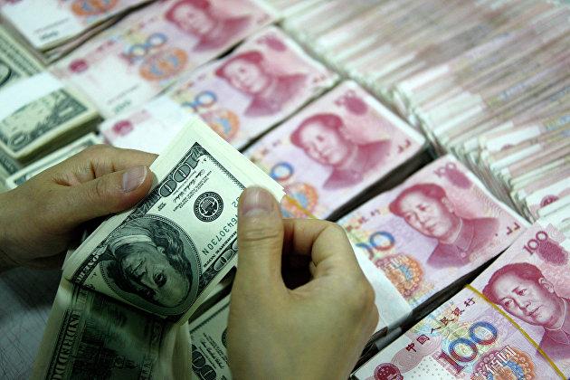 #Банковский служащий пересчитывает доллары рядом с пачками юаней