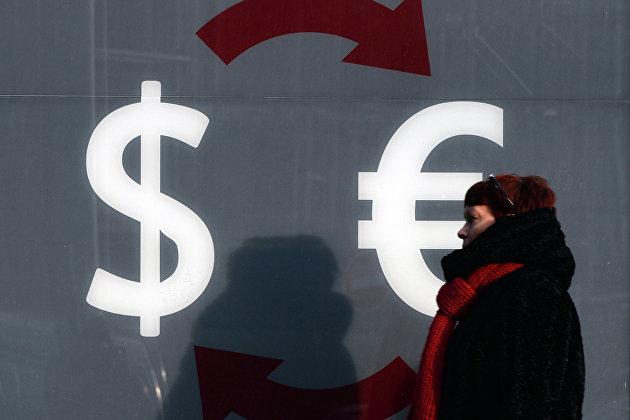 *Знаки доллара и евро на стене пункта обмена валюты в Москве