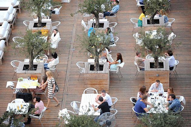 Посетители за столиками в летнем кафе