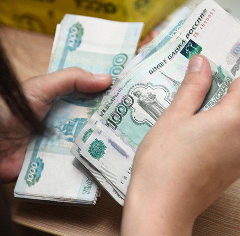 Работник почтамта пересчитывает деньги