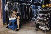 Продавщица одежды на китайском рынке во время обеда