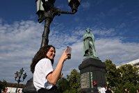 Девушка со смартфоном на Пушкинской площади в Москве
