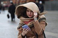 Девушка со смартфоном, ветер