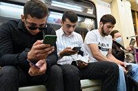 Мужчины со смартфонами в вагоне московского метро