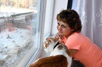 Женщина с кошкой в своей квартире