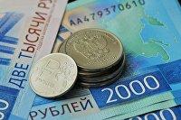 Монета номиналом 1 рубль и банкноты номиналом 2000 рублей
