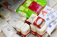 Мешки и пачки с сахаром на полке магазина