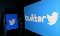Логотип социальной сети Twitter на экранах мобильного телефона и компьютера