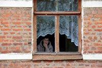 Женщина смотрит из окна своего дома в городе Чекалин Тульской области
